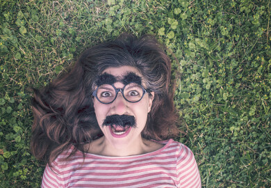 Aerial shot of woman wearing Groucho Marx glasses and lying face up on lawn