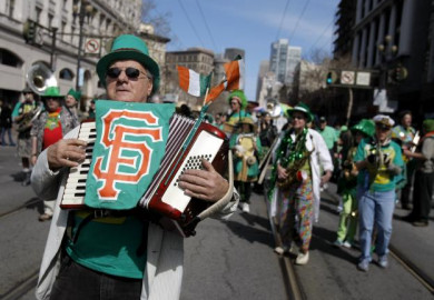 Man playing accordion and wearing green hat in a st patricks day parade