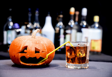 small jack o lantern with a straw drinking a glass of whiskey