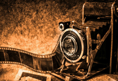 Antique camera and unravelled roll of film all in sepia tones