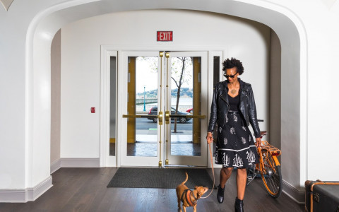woman walking out of the doors with a dog