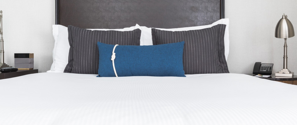 guest room with white linens and blue accent pillow