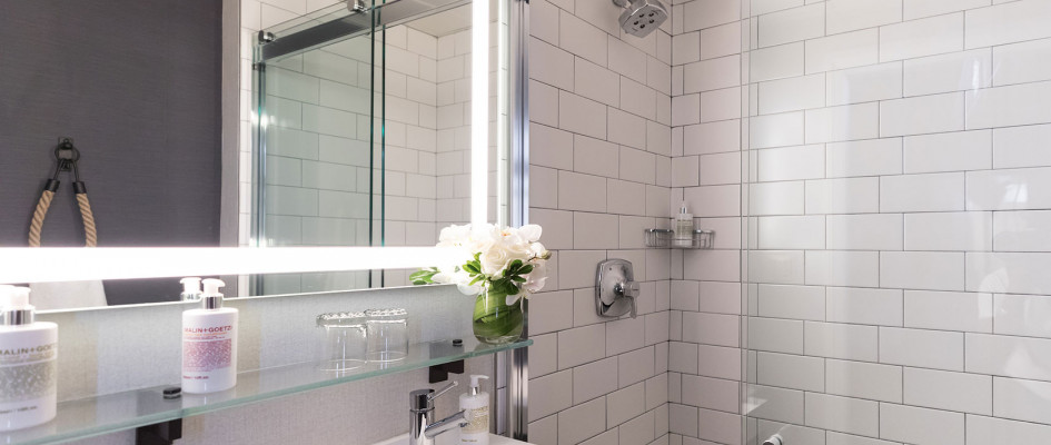 Modern bathroom with white tile and glass shower partition
