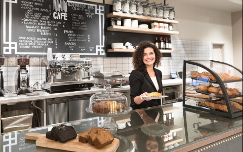 Woman at the cafe counter holding a pastry