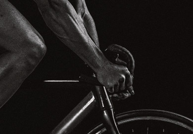 Black and white image of hands on bicycle handle bars