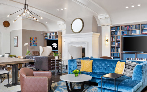 Lobby modern seating area with blue sofa and wall of bookshelves