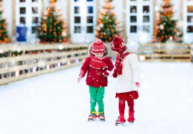 two kids hold hands while ice skating