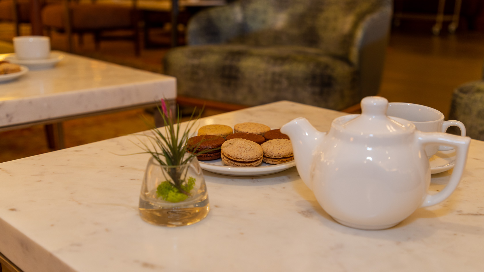marble tabletop with white tea kettle and cookies