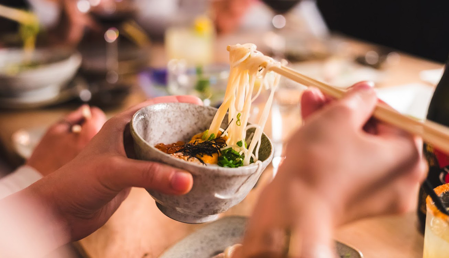 person holding a bowl eating noodles with chopsticks