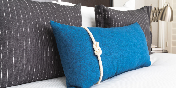 close up of the king bed with white linens and modern gray and blue pillows