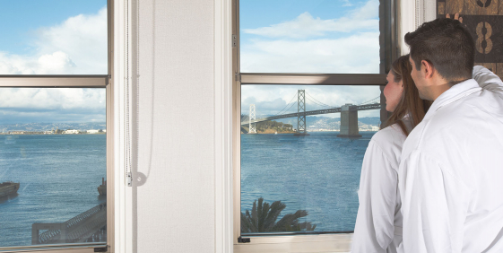 couple in bathrobes looking out of the large windows into the san francisco bay