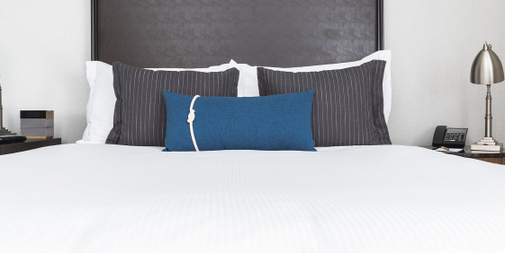 close up of the queen bed with white linens and blue and grey pillows