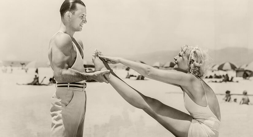 Vintage photo of woman stretching on beach with man