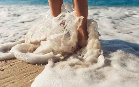feet in the sand and water