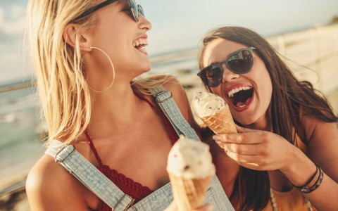 girls laughing and eating ice cream on the beach