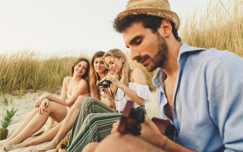 friends sitting on the beach playing guitar and looking at photos on a camera