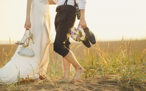 bride and groom walking in grass with shoes off