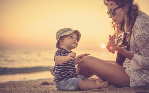 mother and little boy sitting on beach at sunset