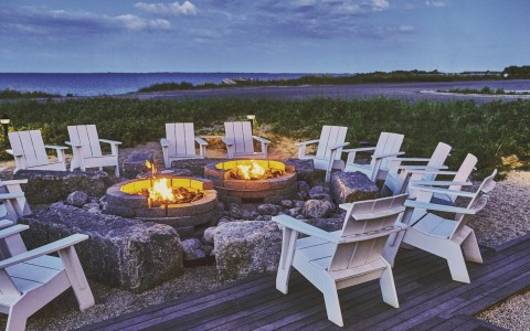 fire pit and white chairs surrounding it