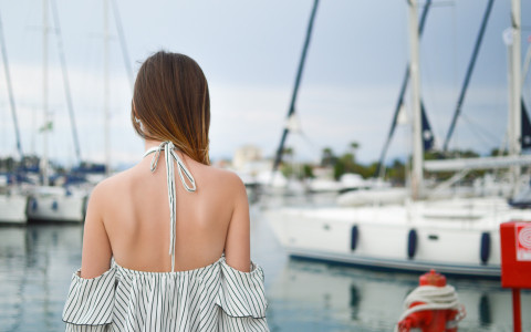 Behind view of a woman walking on a dock towards sailboats