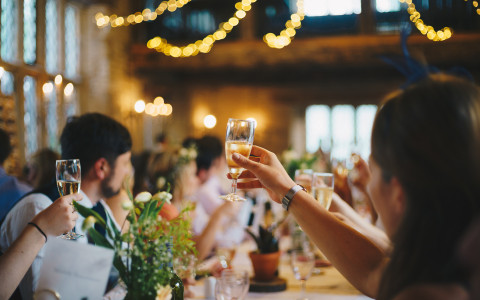 Wedding guests raising their glasses of champagne for a toast