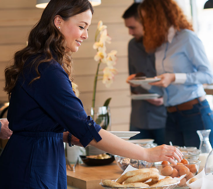 woman selecting food on the buffet