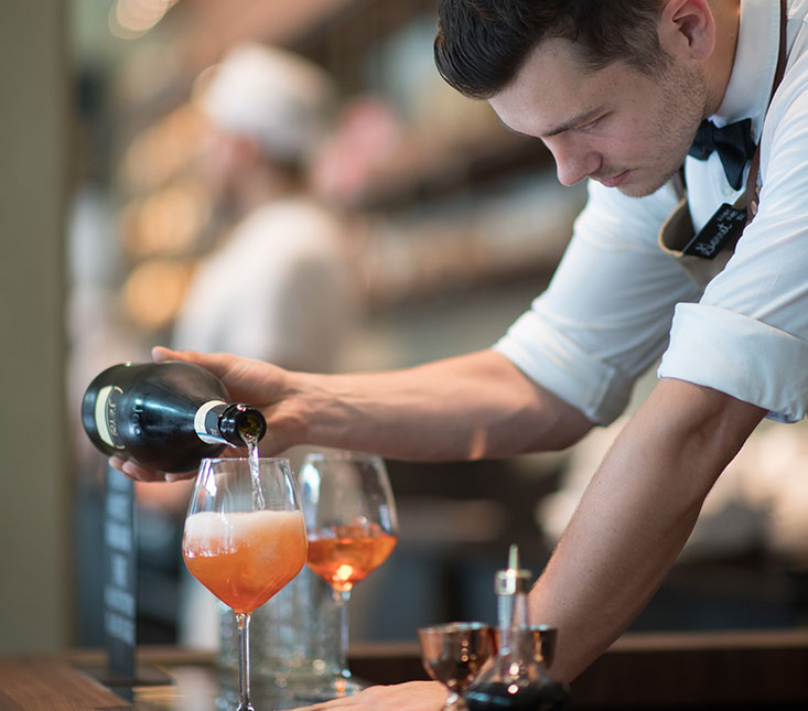a bartender pouring wine into a wine glass