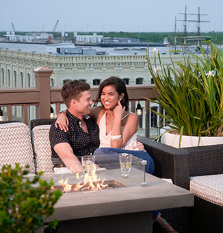 A couple sitting together on a couch near a fire at a rooftop bar