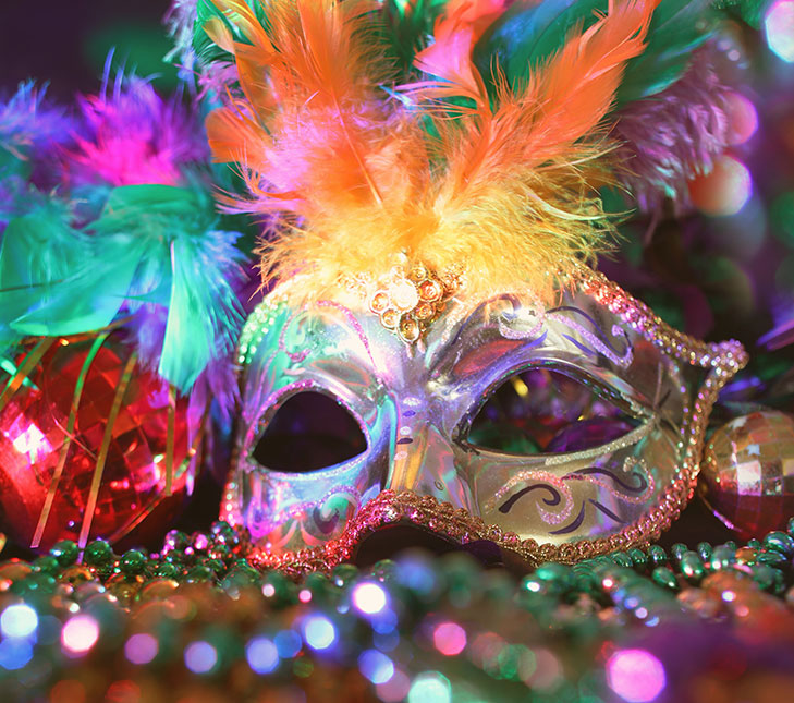 A decorative eye mask with colorful feathers sitting next to colorful beads