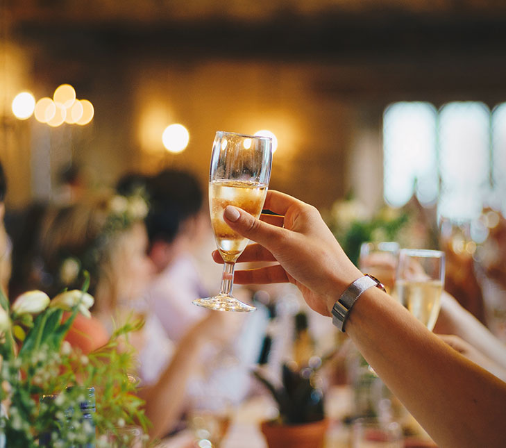 A person raising a glass of champagne for a toast