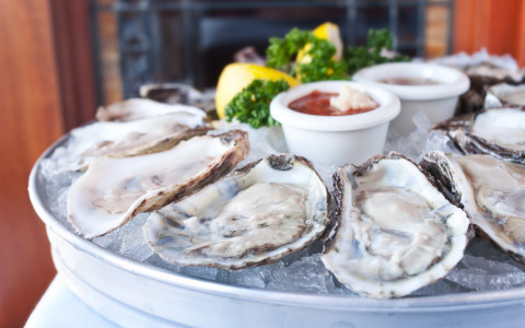 Plate of oysters with cups of dipping sauce, lemons, and garnishing in the center of the plate