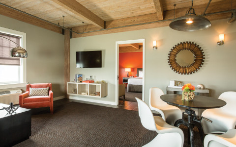 Interior of a guest suite living room area with modern chairs and table, chair, tv, and a view of the door leading into the bedroom
