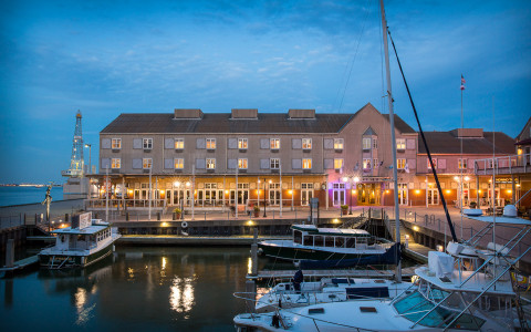 Exterior view of Harbor House at night as seen from the marina
