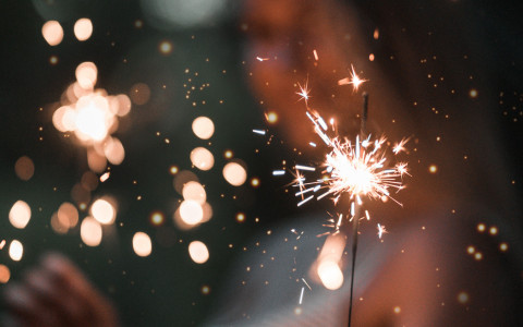A woman holding a lit sparkler at night
