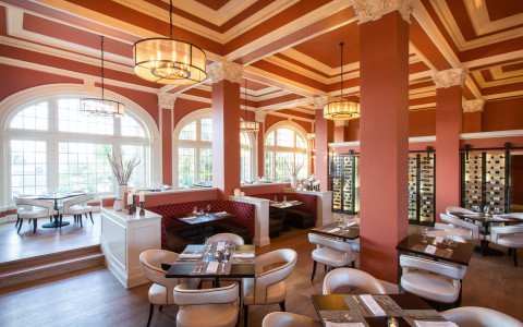 An elegant dining area with muted red painted walls, white trim, booth and table seating, and a wine cellar in the back