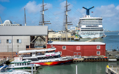 A Carnival Triumph cruise ship docked at the port near other boats and sailboats