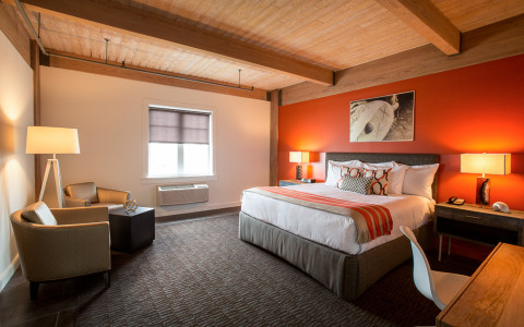 Interior of a guest room with a king bed, cushioned chairs, nightstands, and a desk area. The room has an orange accent wall and wooden ceilings.