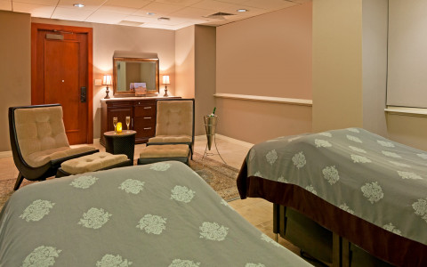 A spa room with two spa beds, cushioned chairs, and champagne on the side table