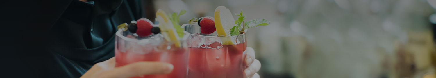 Close up of someone holding two fruity cocktail drinks garnished with lemons, raspberries, blueberries, and mint