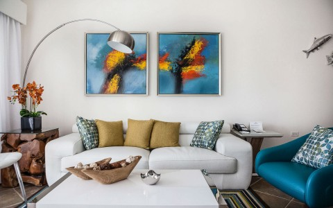 long white couch with colorful accent pillows and a blue painting on the wall