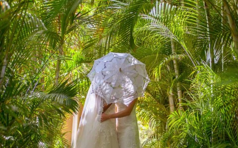 two brides in the woods wit their faces covered by a delicate white umbrella