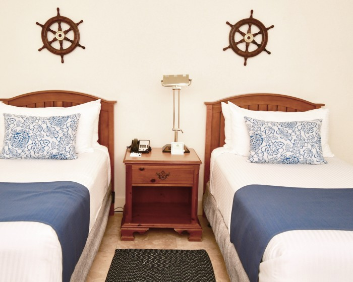 twin beds with blue throw blankets and boat decorations