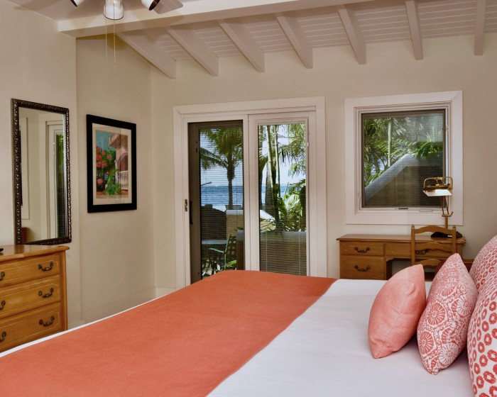king bed with coral throw blanket and glass door to balcony