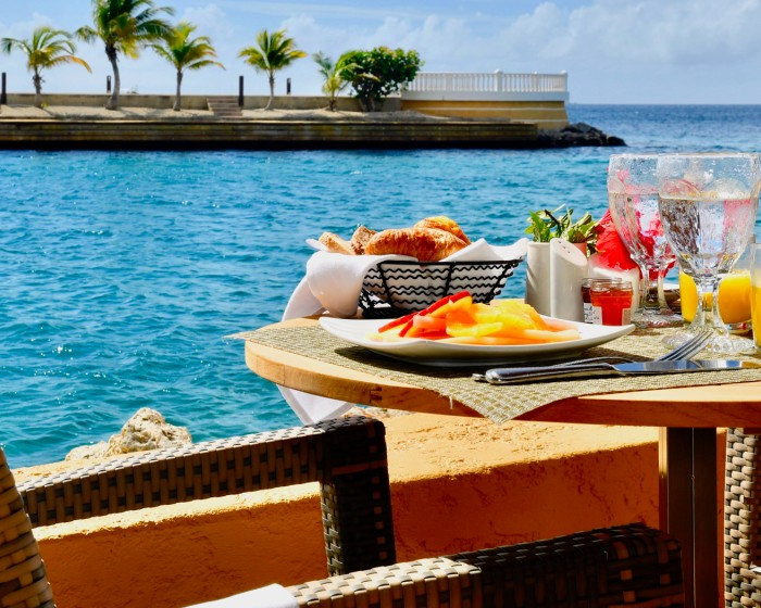 a round table with chairs and colorful breakfast served with a view