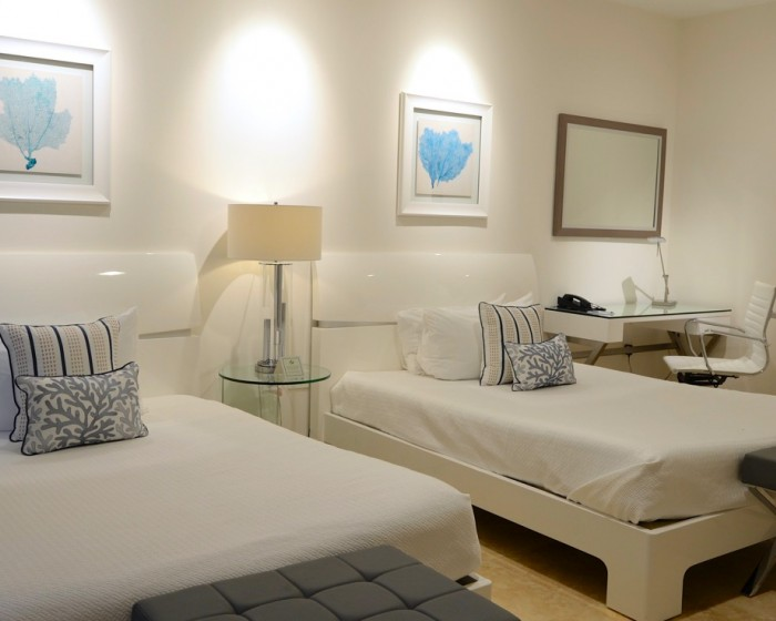 double beds with white linens and white retro furniture
