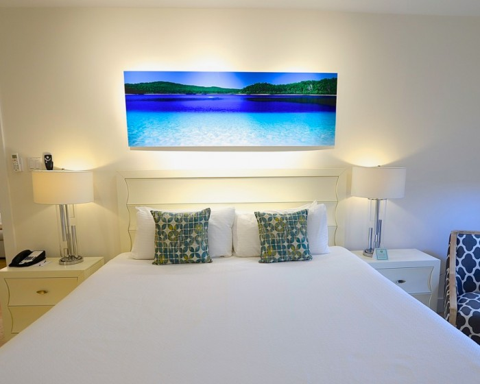 comfortable white linens on a bed with a large painting of the ocean behind the bed