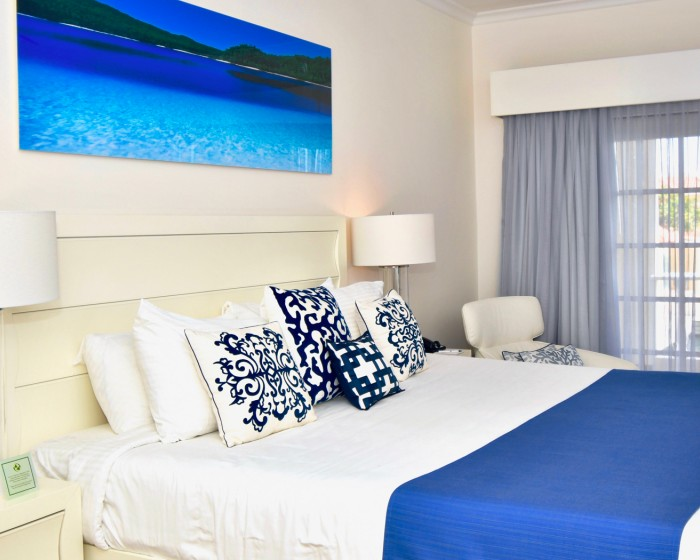 king bed with blue throw blanket and accent pillow and a picture of the ocean on the wall