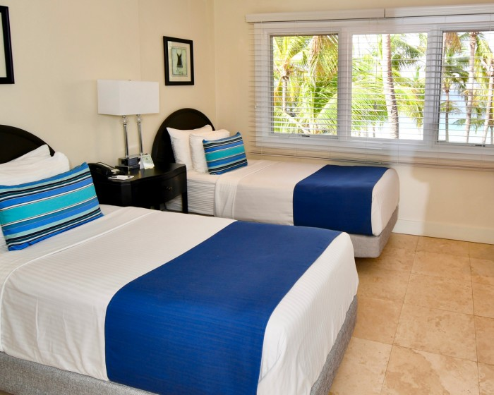 two hotel beds with blue blankets and pillows and tile floor