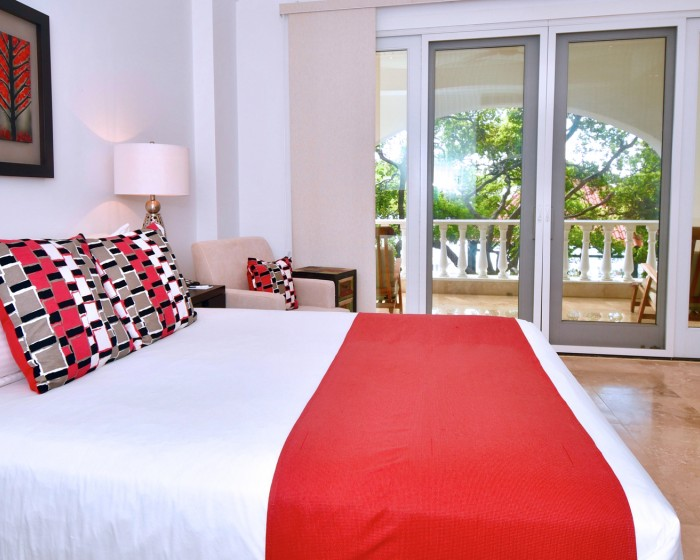 large bed with red accent pillow and throw blanket and a sliding balcony doors