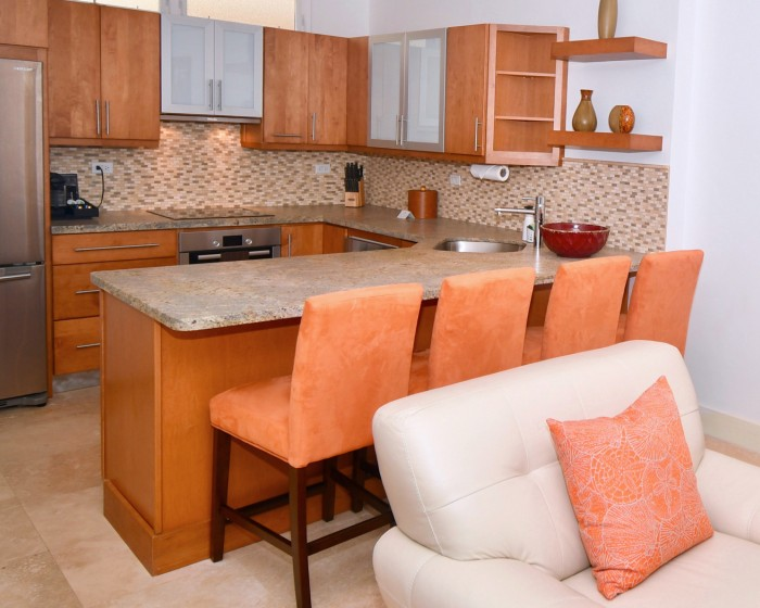 kitchen island with orange high chairs and white couch nearby